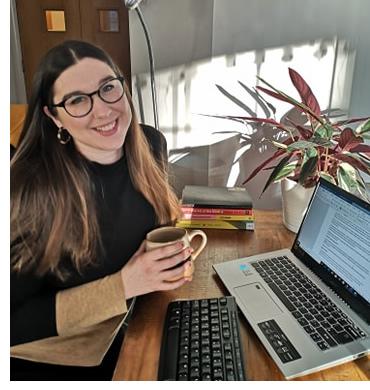 Rachel Baker smiling, sat at her desk