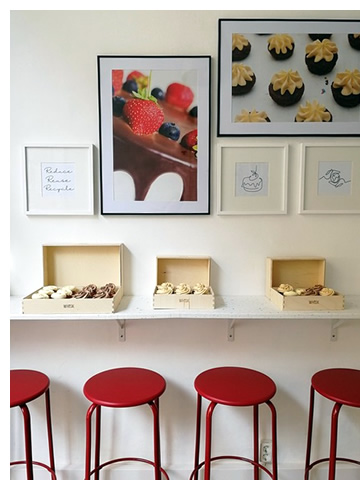 A view of the WHISK shop with pictures of cakes on the wall, a counter  holding wooden boxes of cupcakes and red stools underneath
