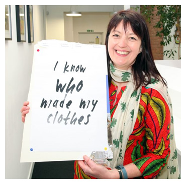 Jo Salter smiling and holding a sign with the text 'I know who made my clothes'