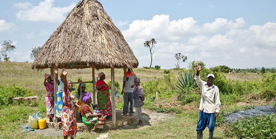 A group of people sitting and standing in Kenyan countryside, smiling and waving to the camera